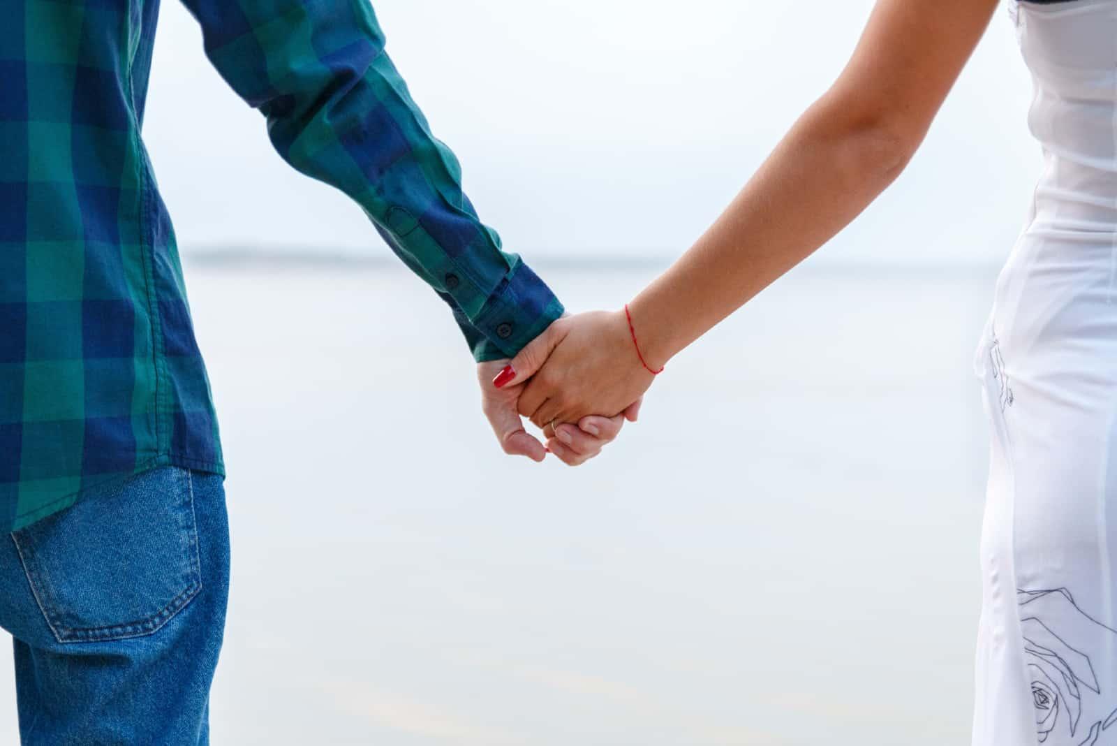 Un homme et une femme se tenant la main près d'un plan d'eau