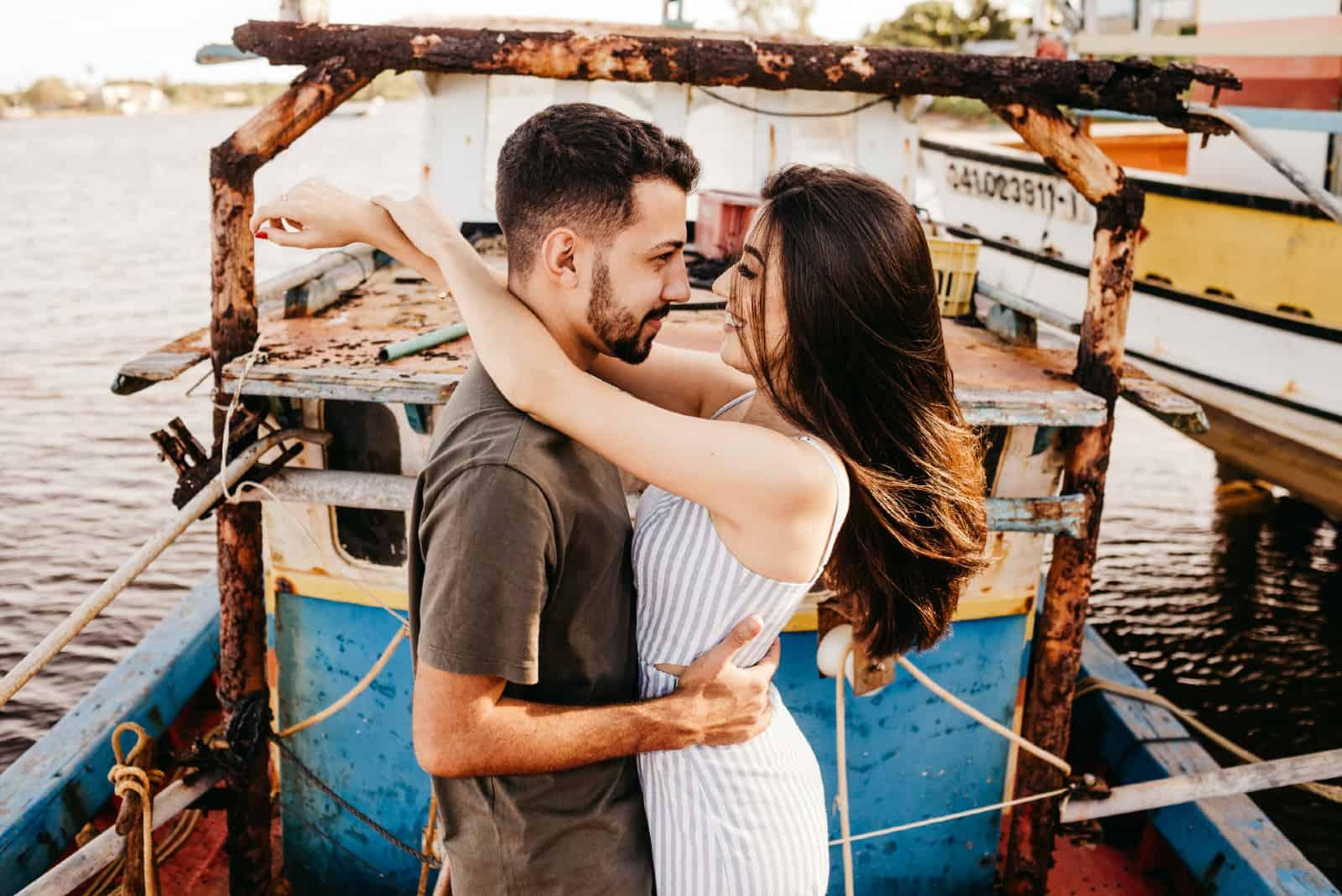 un homme et une femme s'embrassant en se tenant près de l'eau