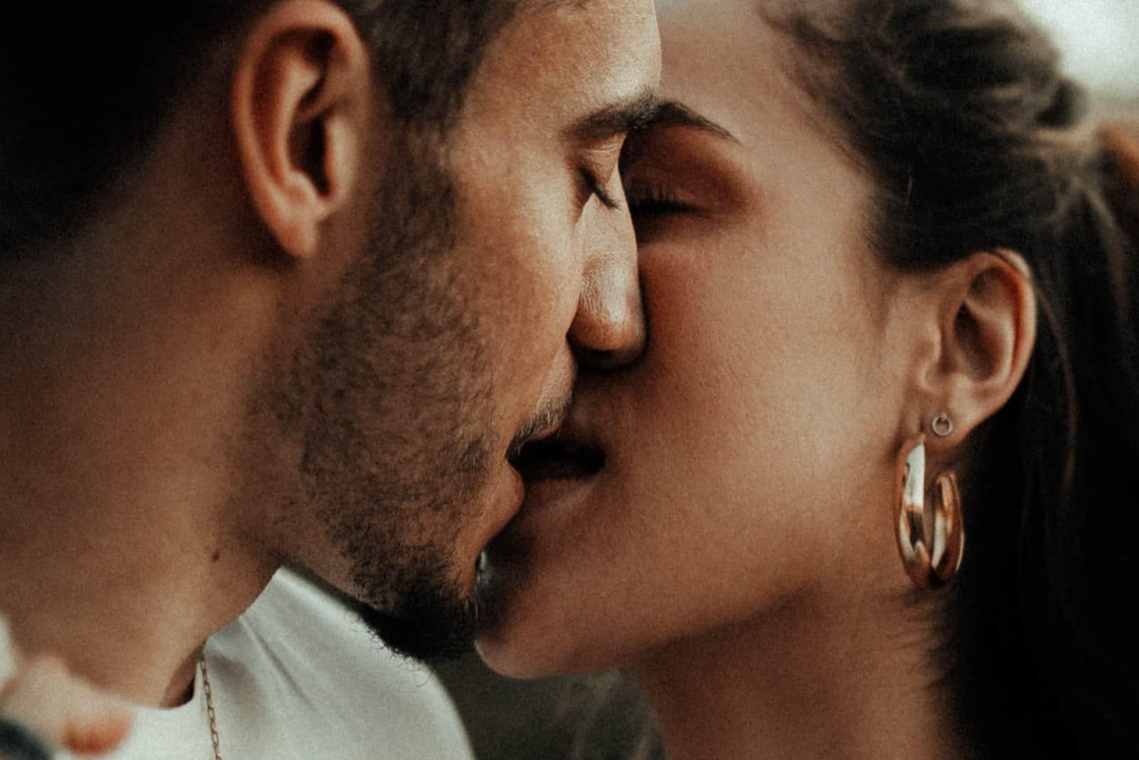 homme et femme avec boucle d'oreille en or s'embrassant