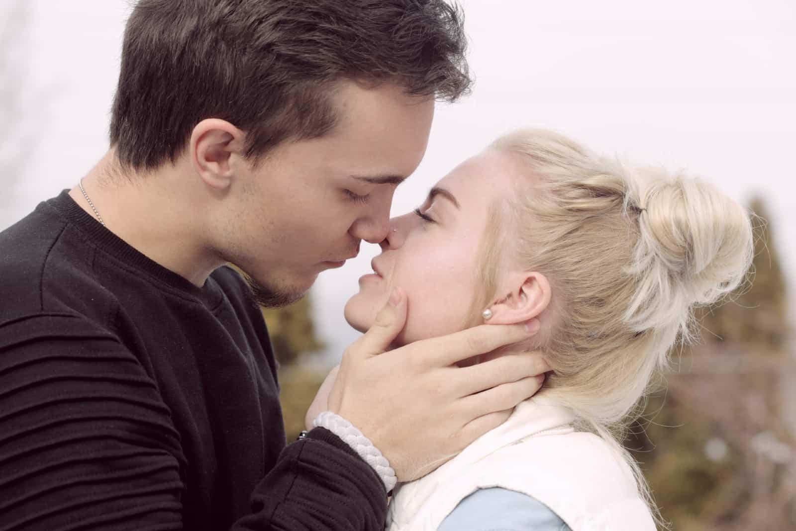 homme et femme sur le point de s'embrasser en plein air