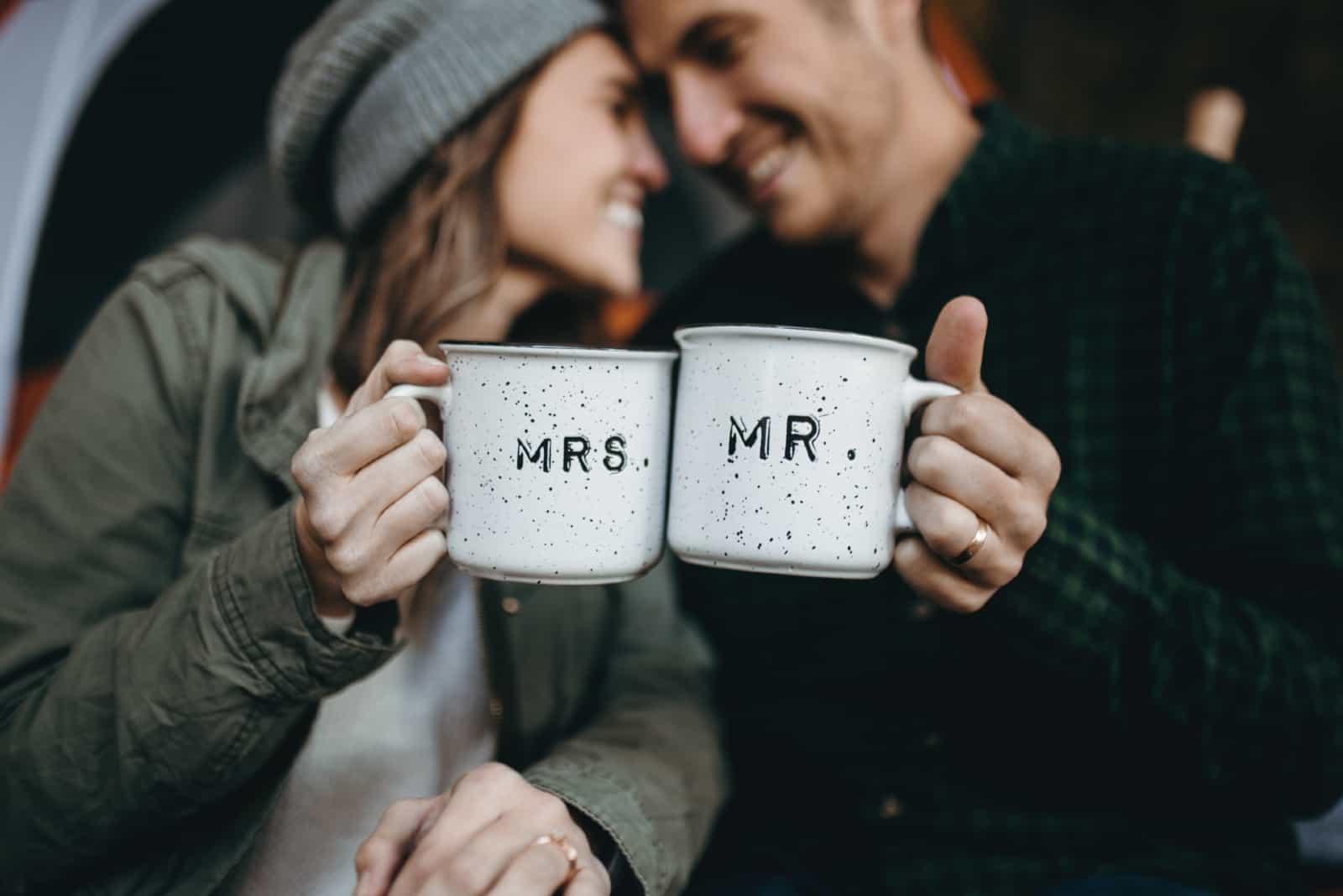 homme et femme souriant en tenant des tasses