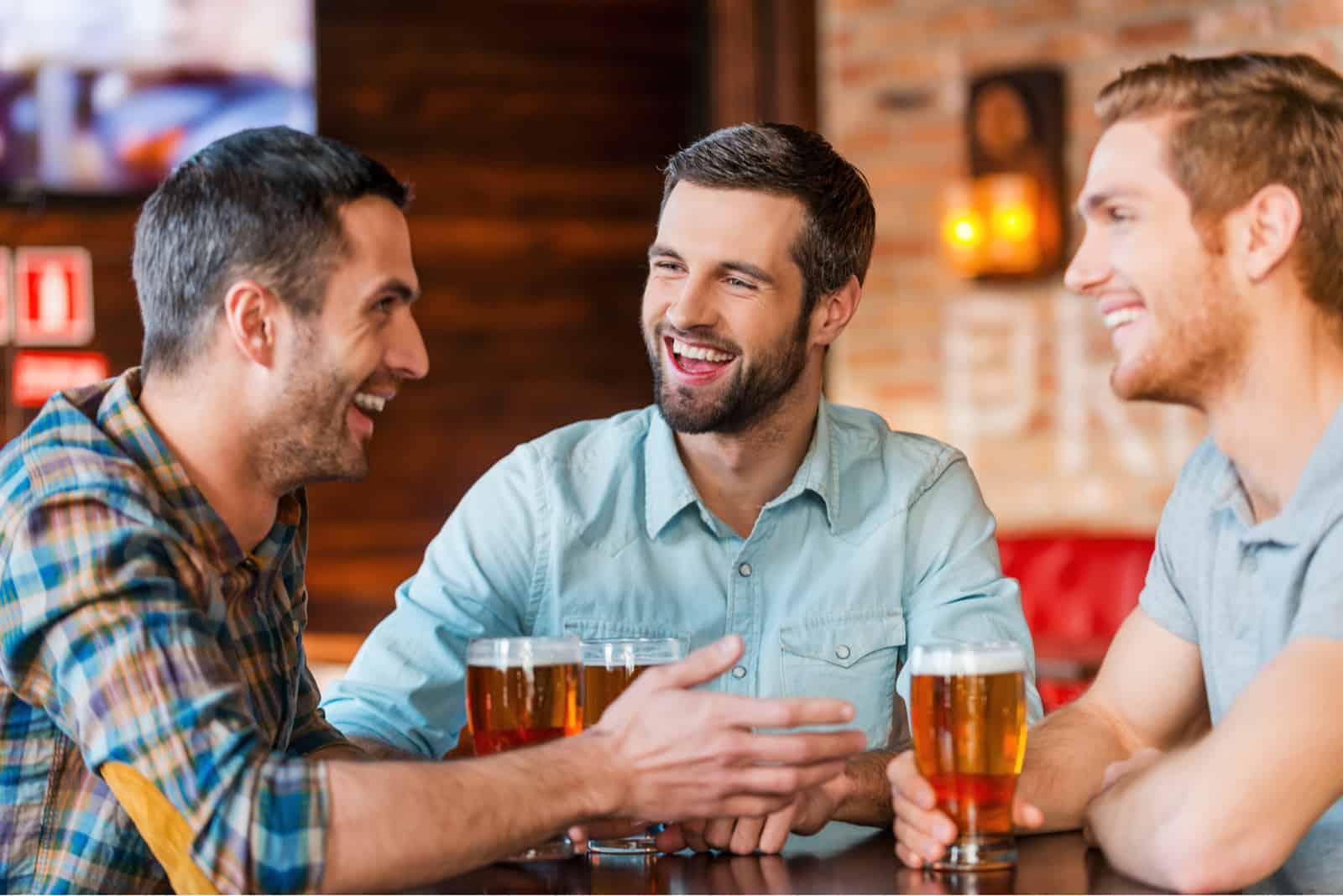 des amis s'assoient et discutent autour d'une bière