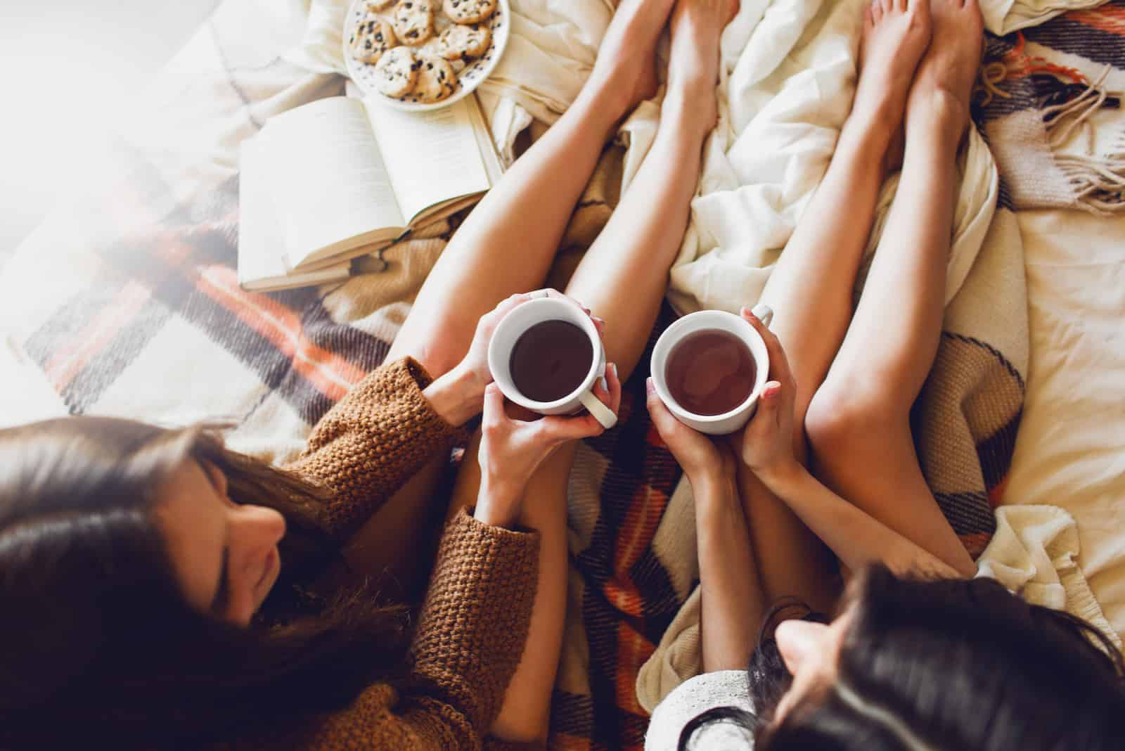 deux soeurs sur le lit avec de vieux livres et une tasse de thé dans les mains