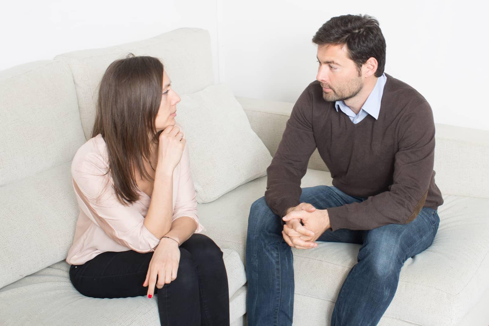 homme et femme parlant assis sur un canapé