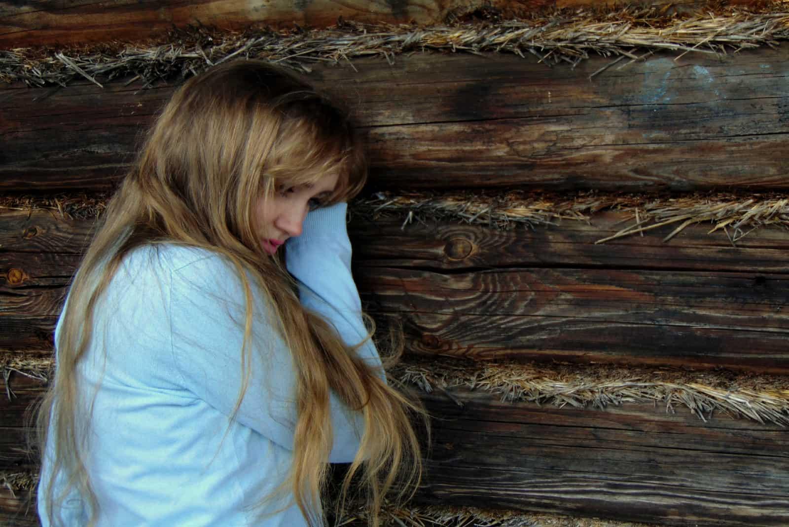 femme triste appuyée sur un mur en bois
