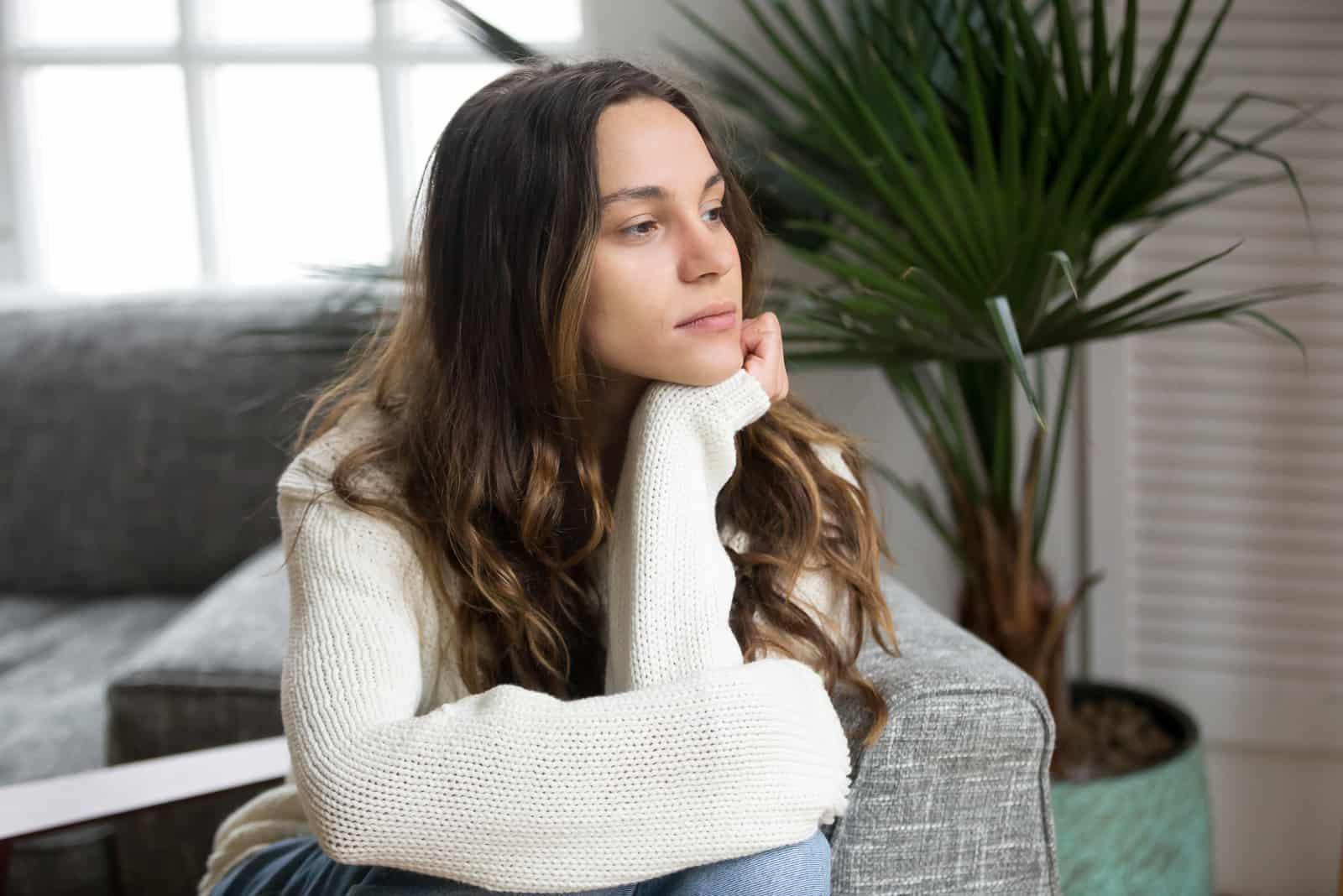 femme triste en chandail blanc assise à l'intérieur