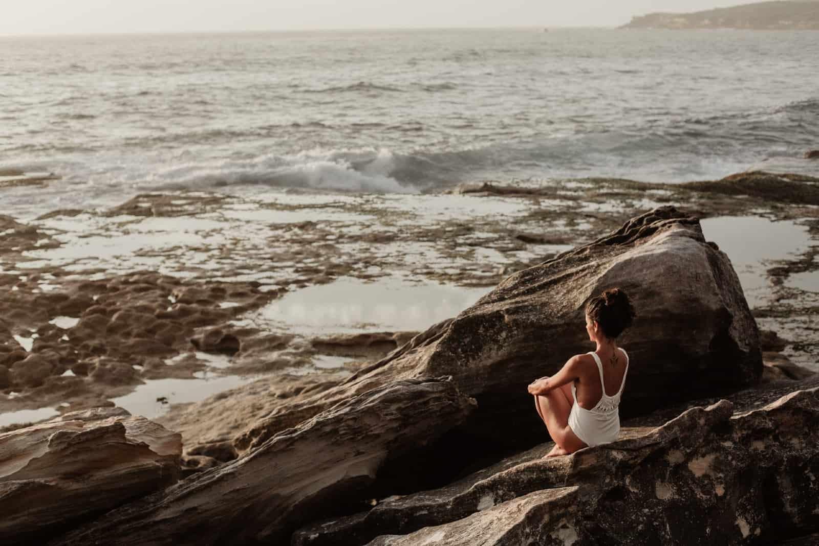 femme assise sur un rocher regardant la mer