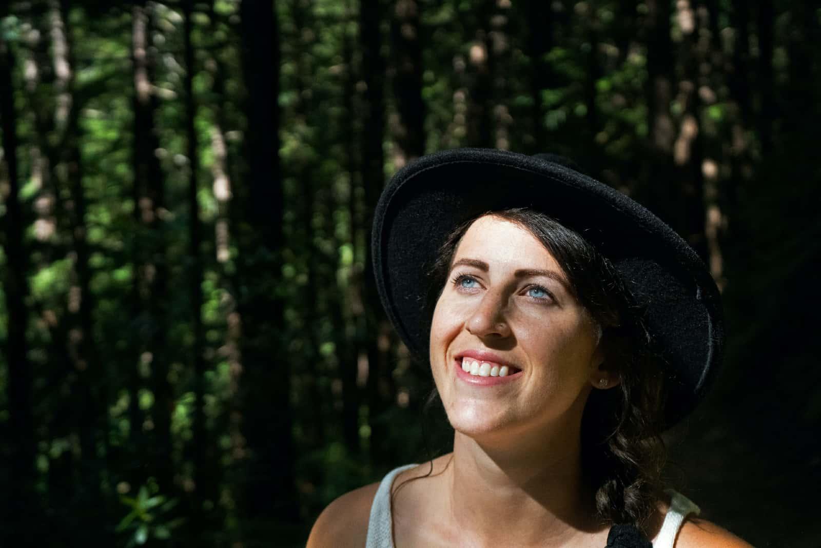 femme aux yeux bleus souriant dans une forêt