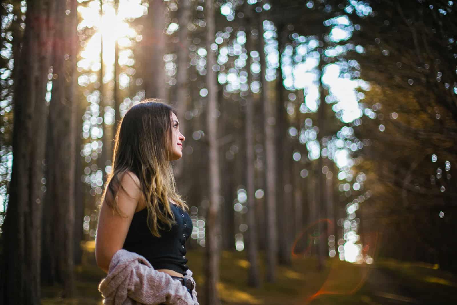 femme en haut noir debout dans la forêt