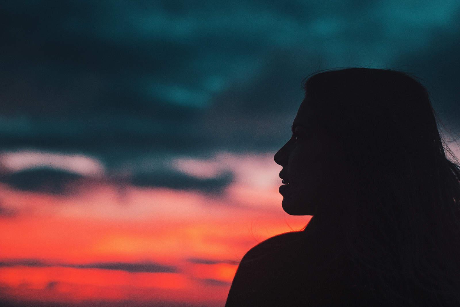 femme debout à l'extérieur pendant le coucher du soleil