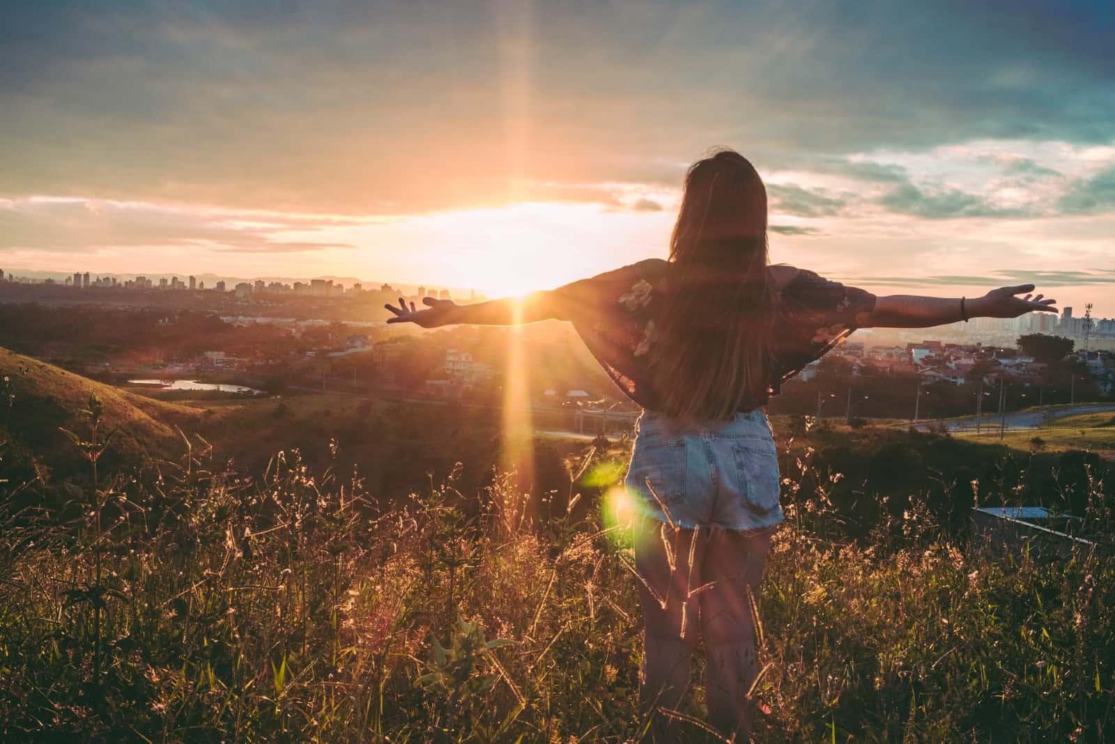 femme debout sur un champ au coucher du soleil