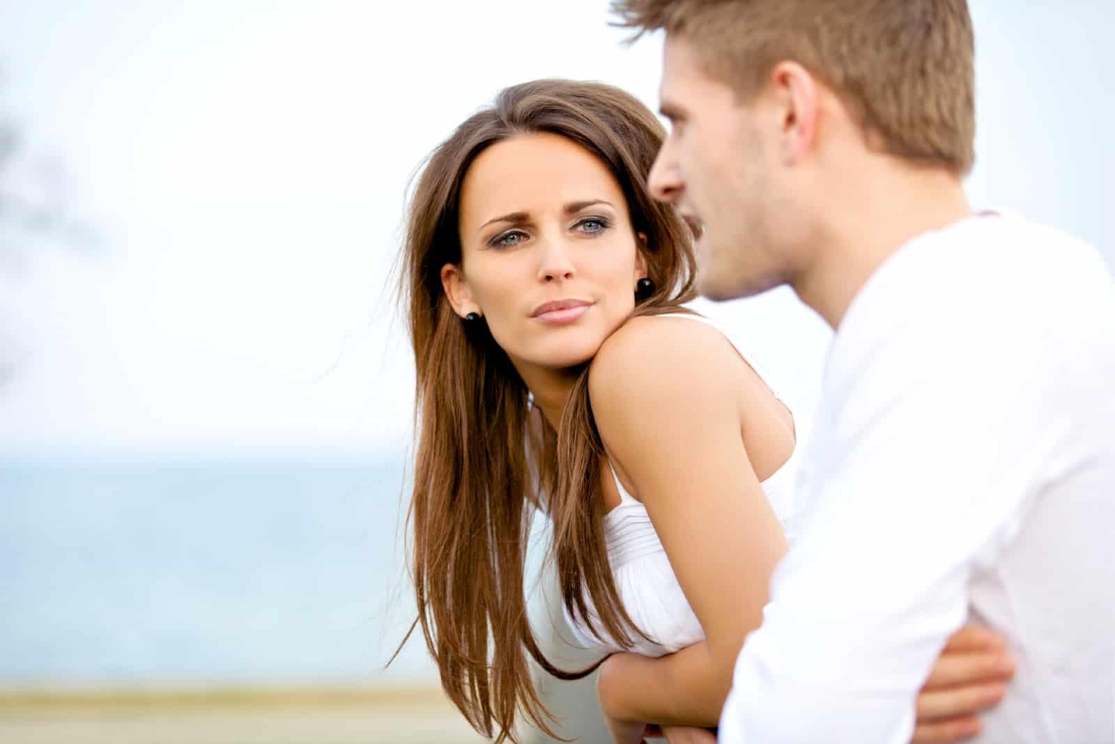 femme en haut blanc écoutant un homme en plein air