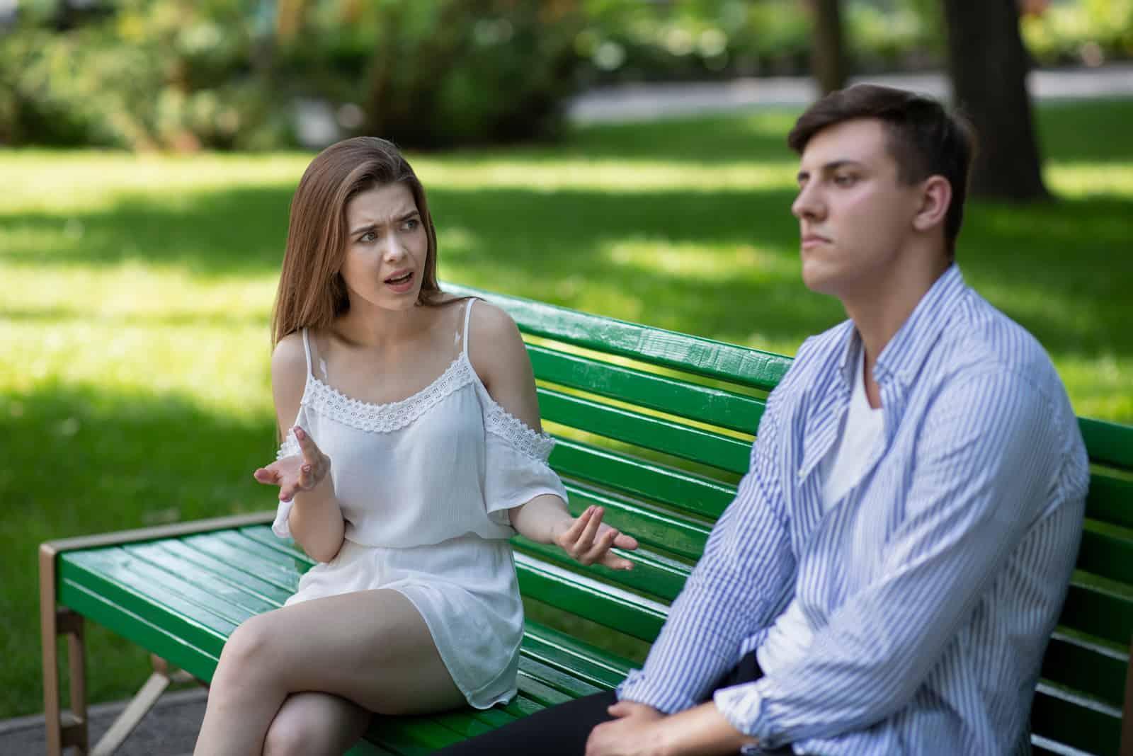 femme hurlant sur un homme assis sur un banc