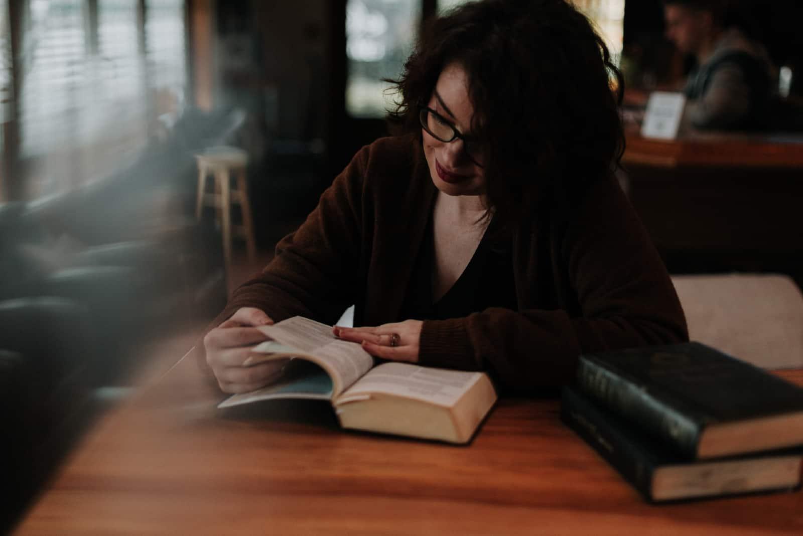 Femme lisant un livre assise à une table