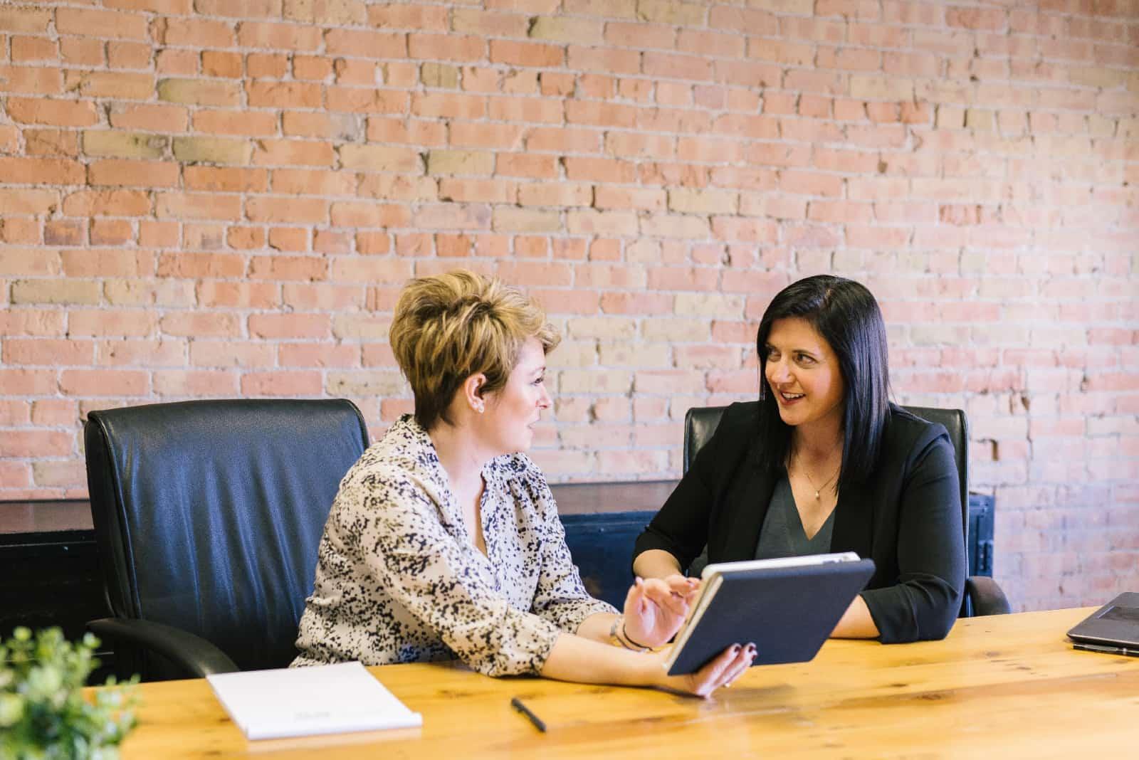 femme parlant à une femme assise dans un bureau