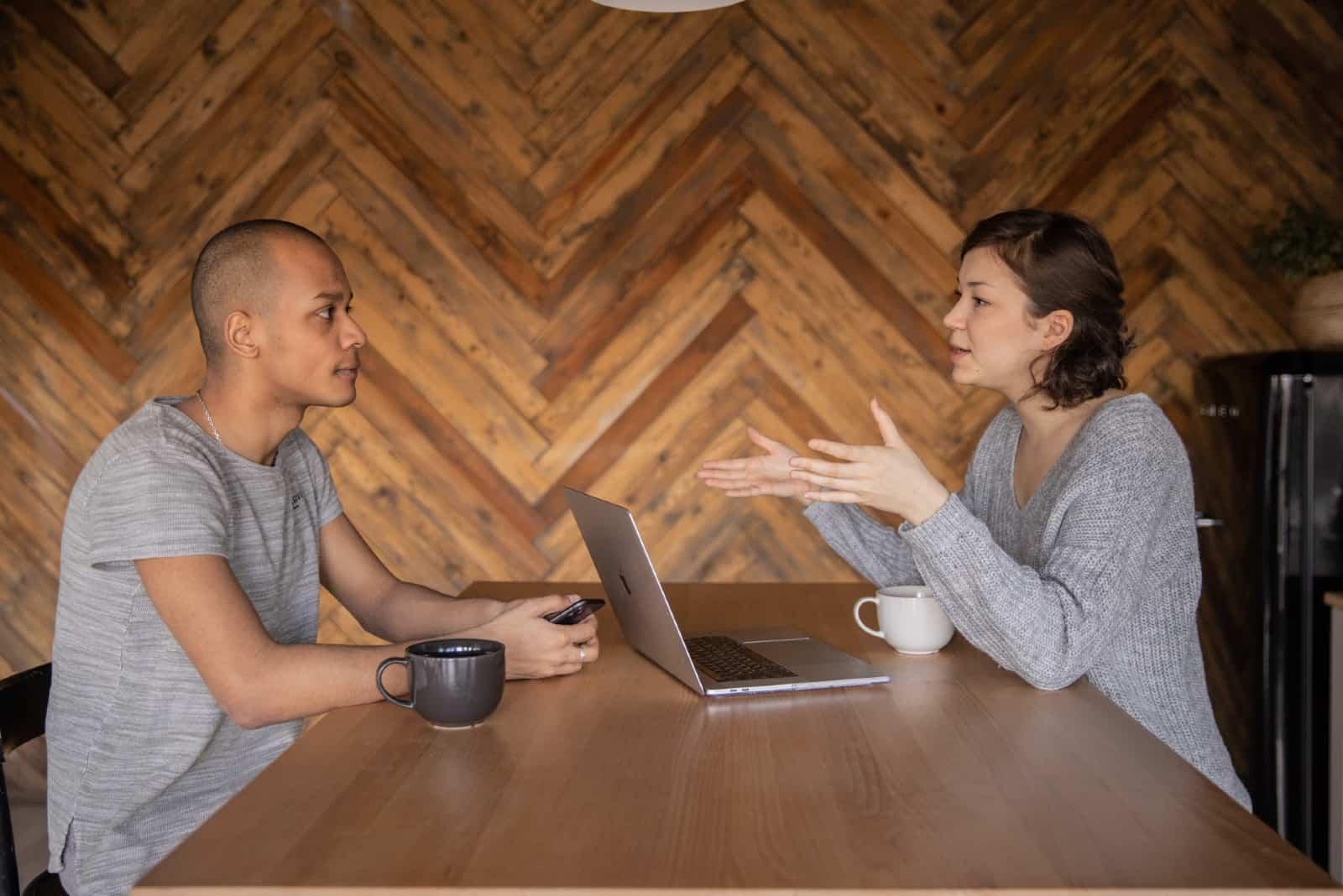 femme parlant à un homme assis à une table