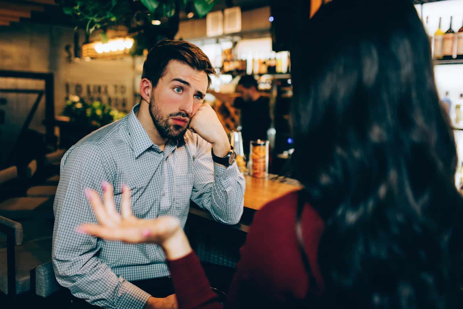 femme parlant à un homme assis dans un bar