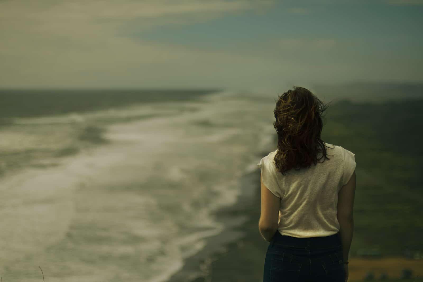 femme en blouse blanche regardant la mer