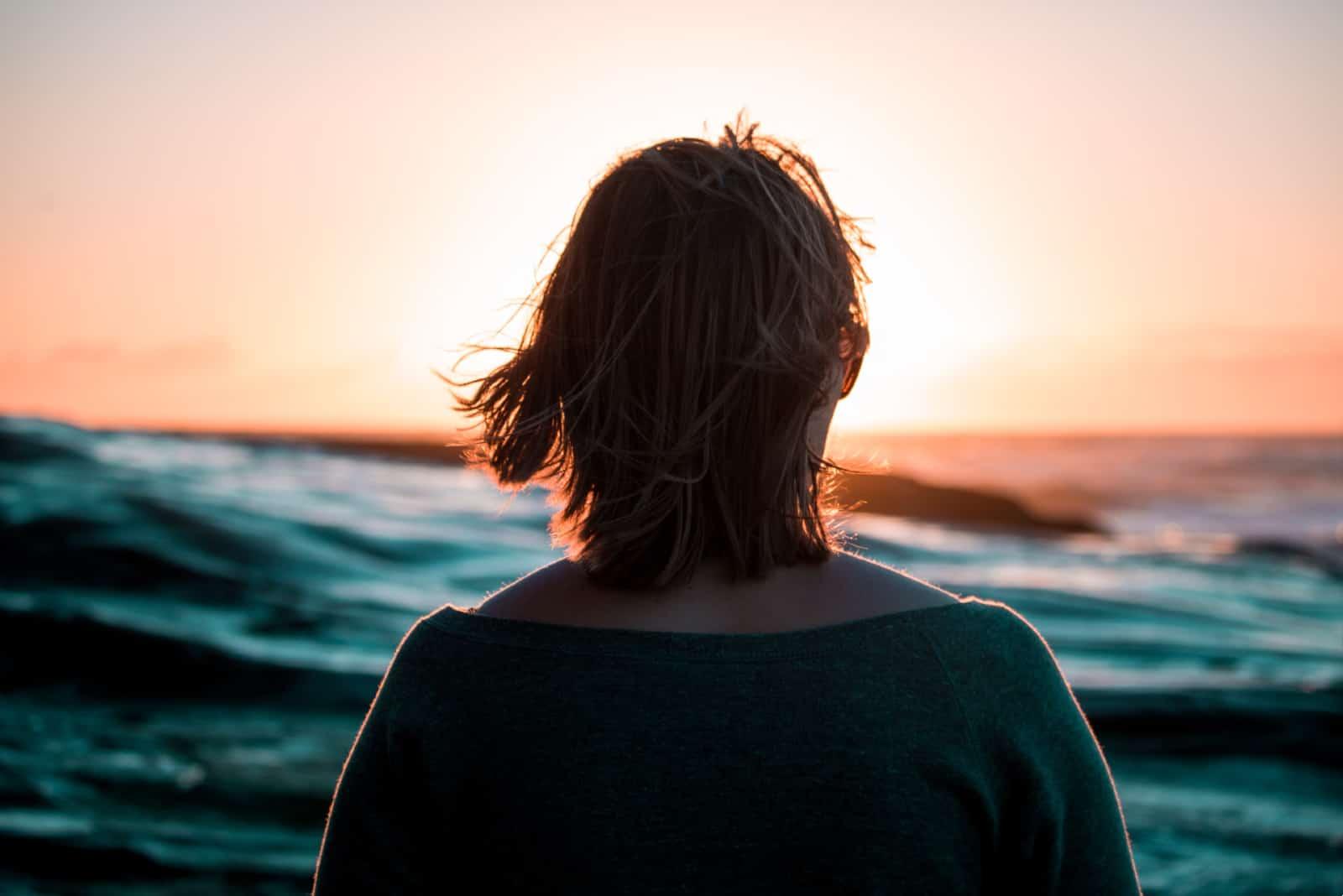 femme regardant la mer pendant le coucher du soleil
