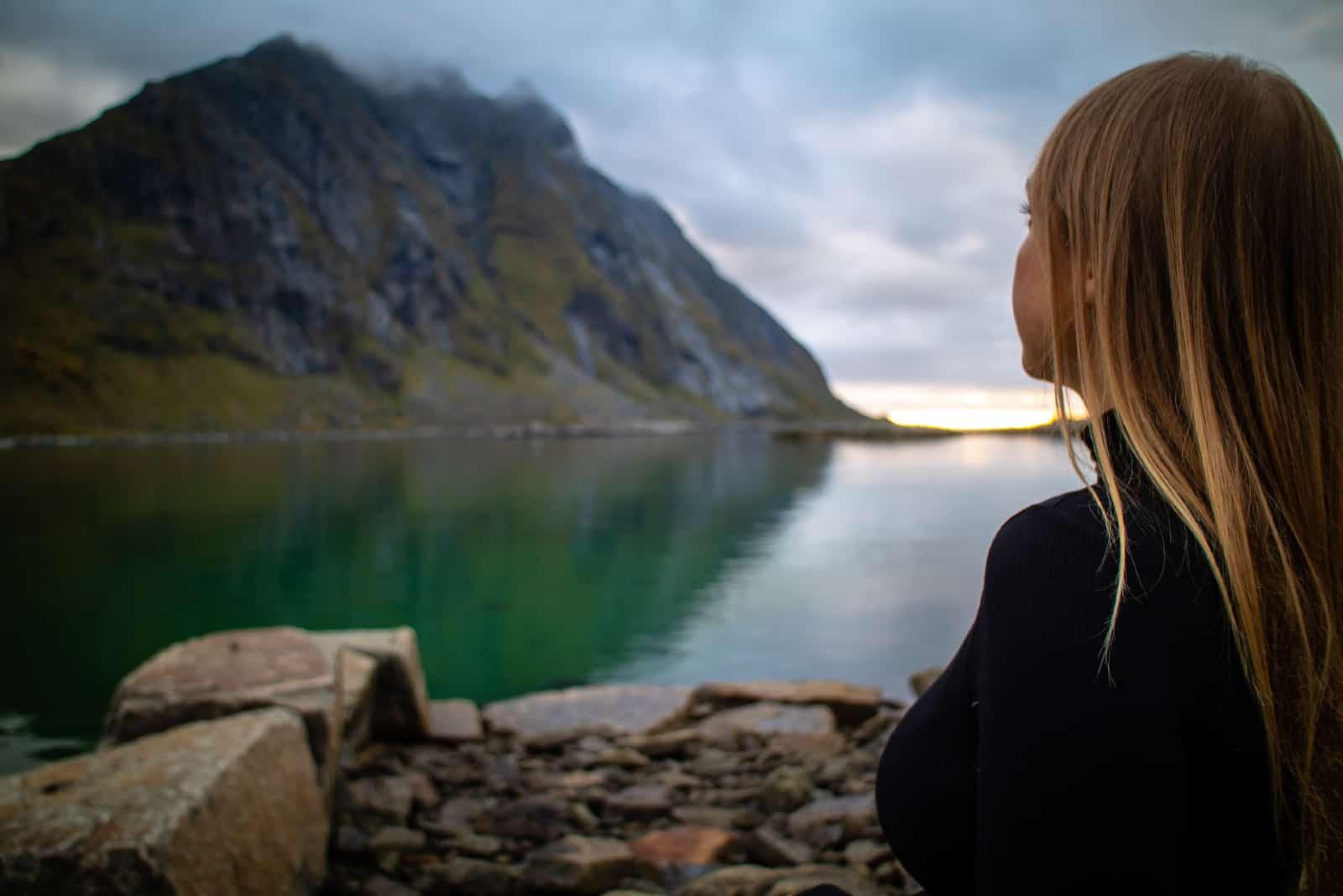 femme assise sur un rocher en regardant la montagne