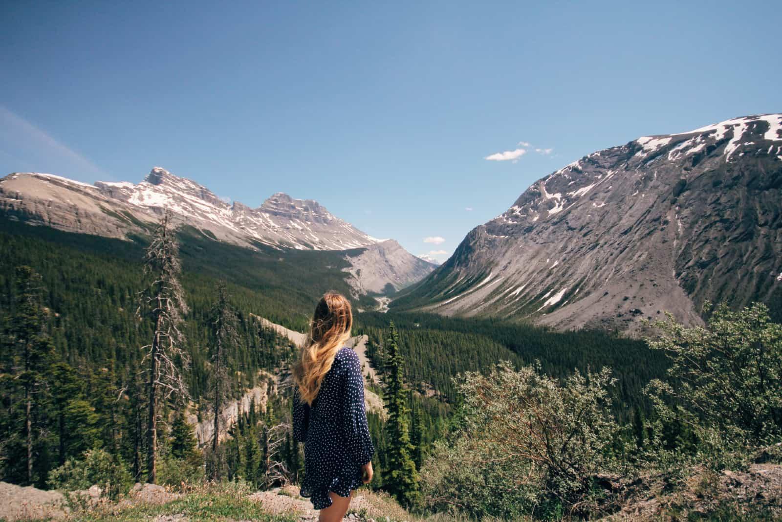 femme en robe bleue à pois regardant la montagne