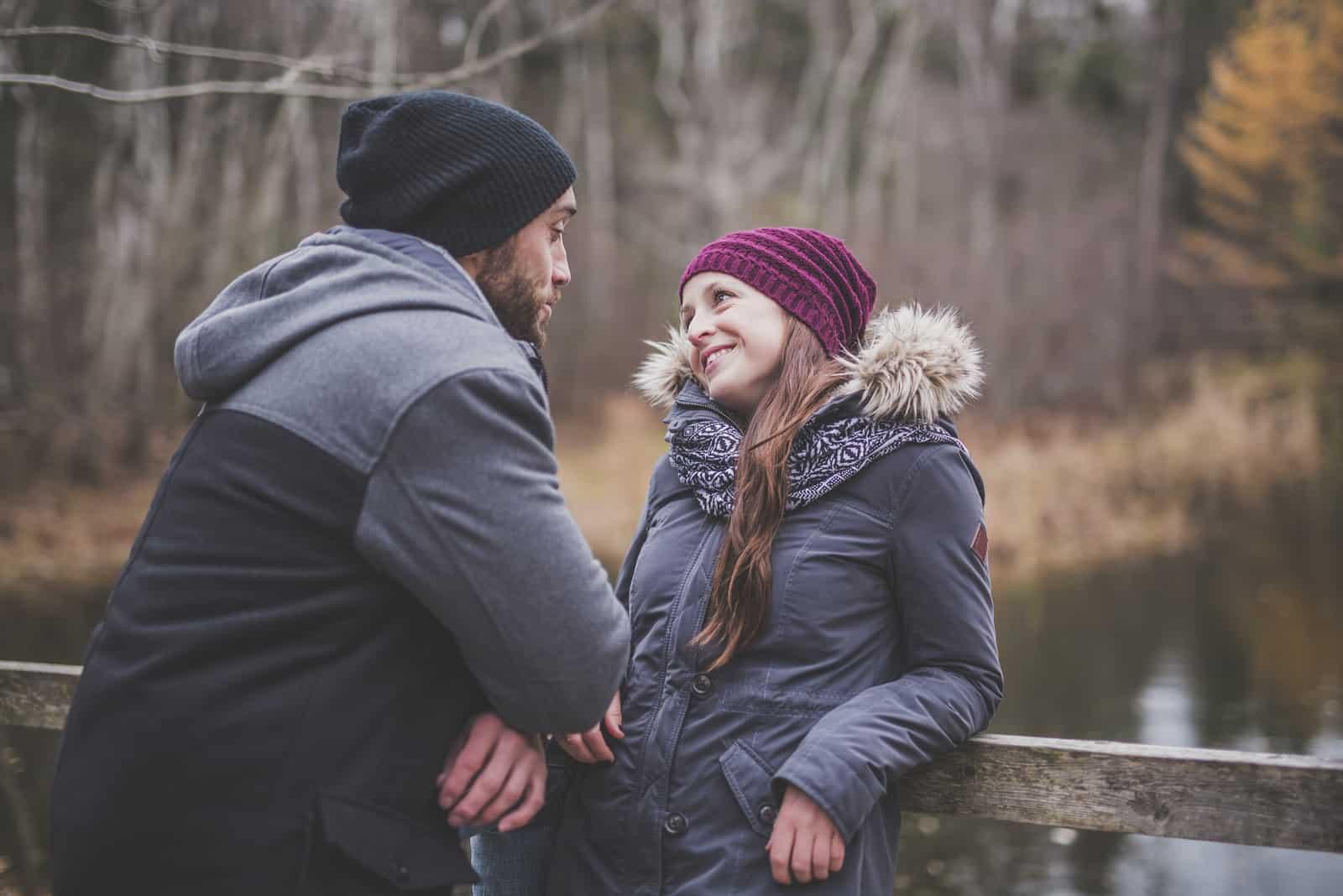 femme heureuse avec une casquette violette regardant un homme