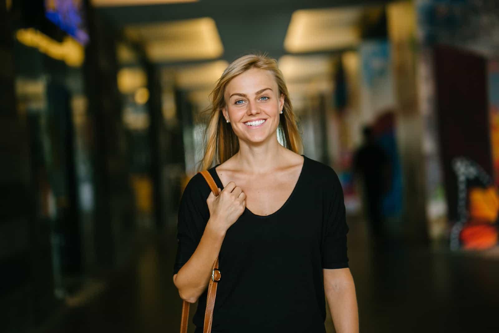 femme blonde avec un haut noir qui sourit