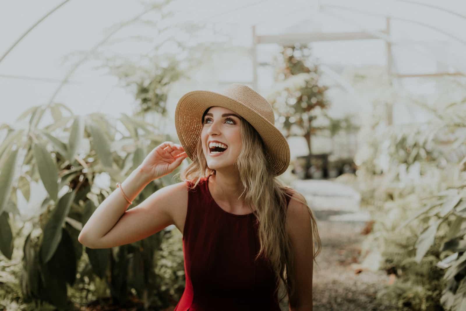 femme avec chapeau souriant en plein air