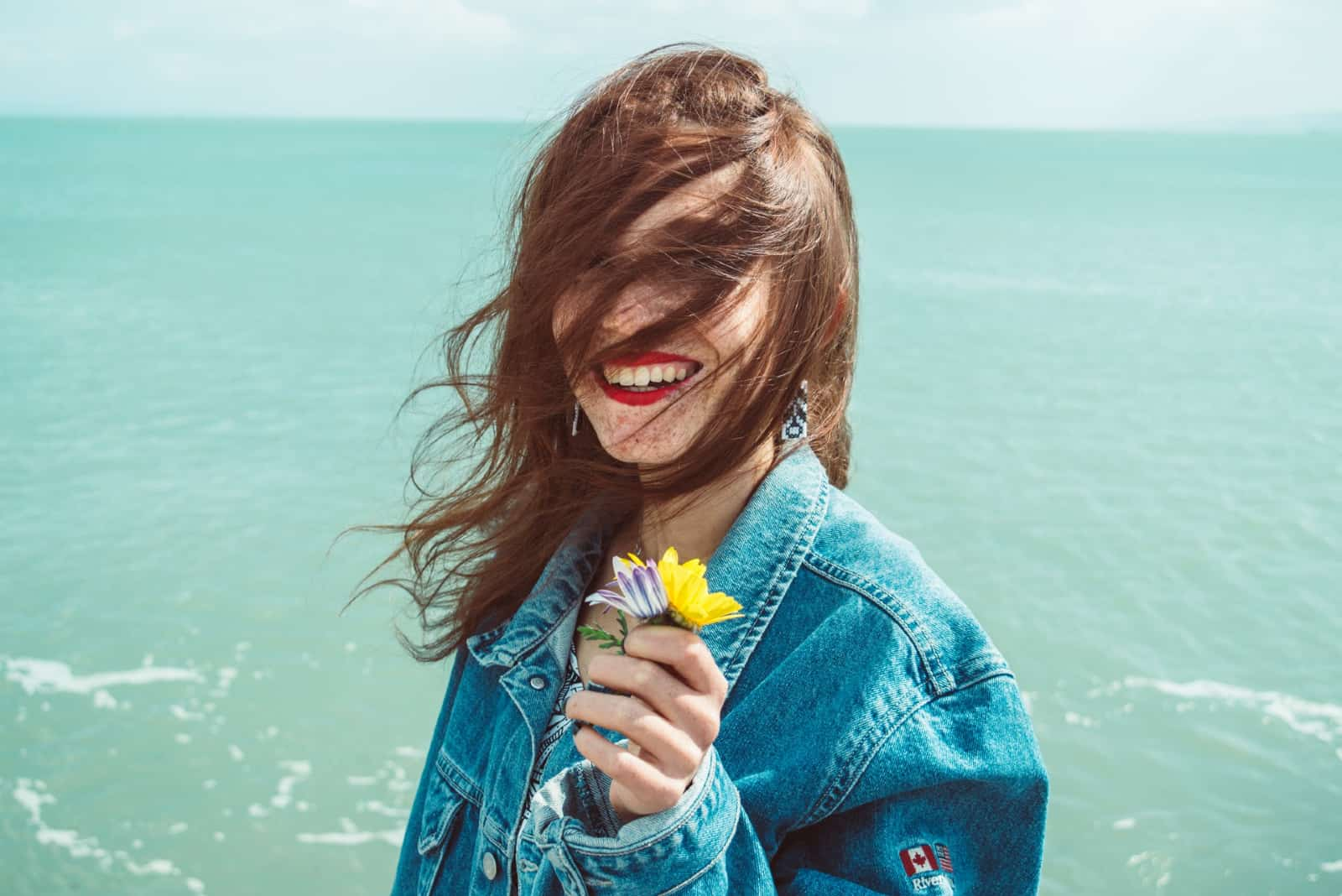 femme en veste en jean souriant en tenant une fleur