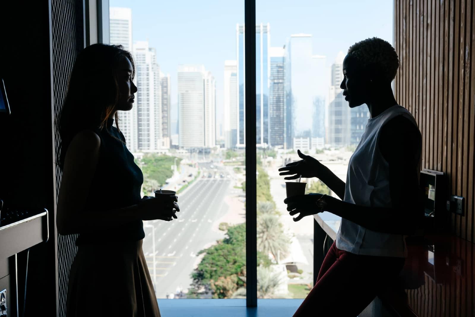 deux femmes prenant un café en se tenant près d'une fenêtre