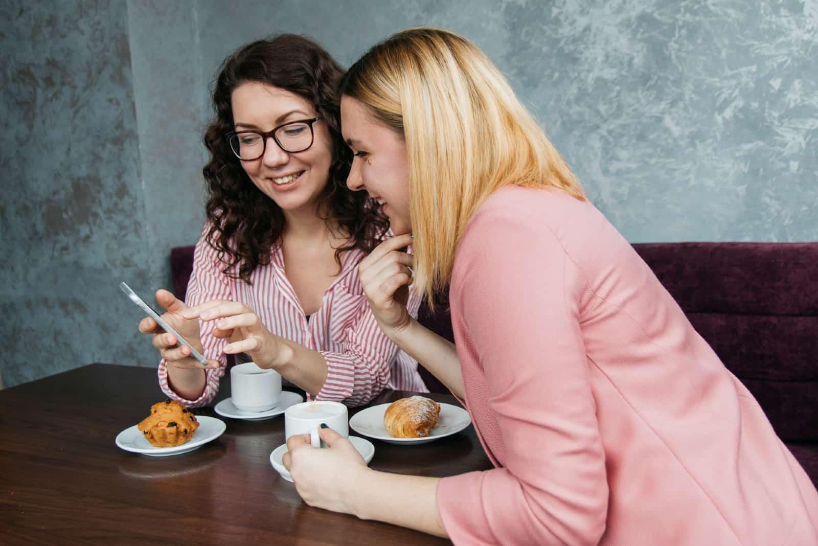 deux femmes regardant un smartphone alors qu'elles sont assises à une table