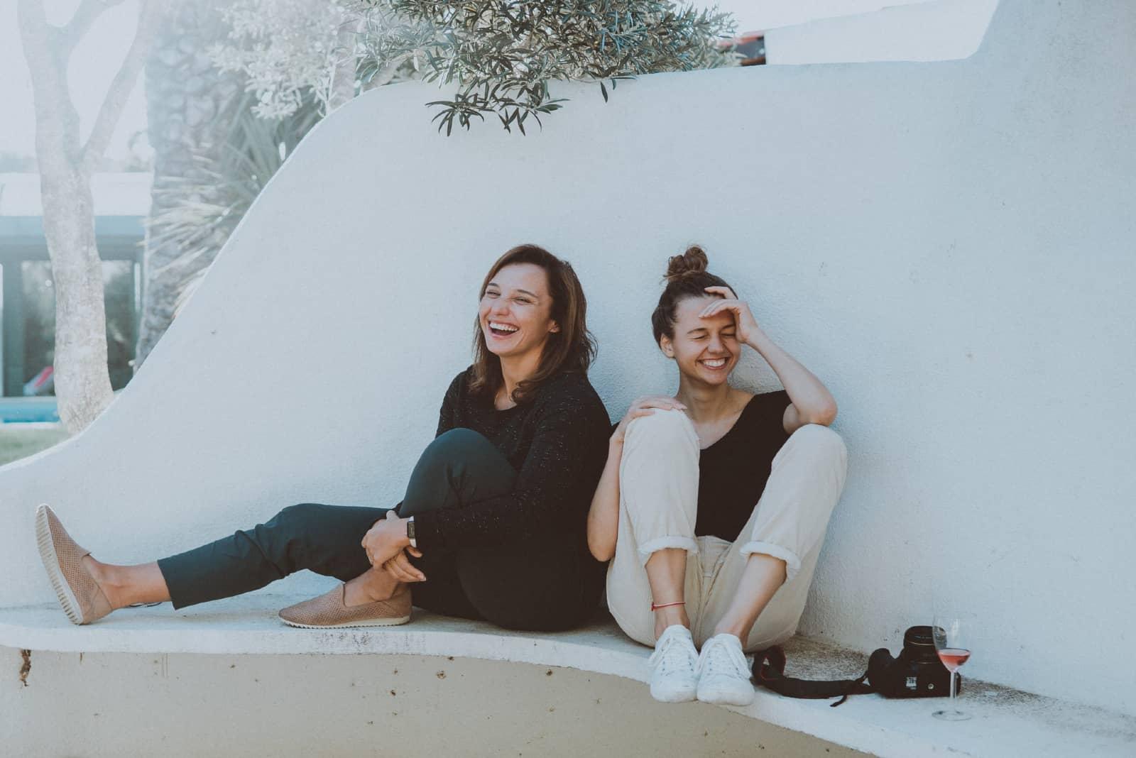 deux femmes qui rient en s'asseyant sur du béton