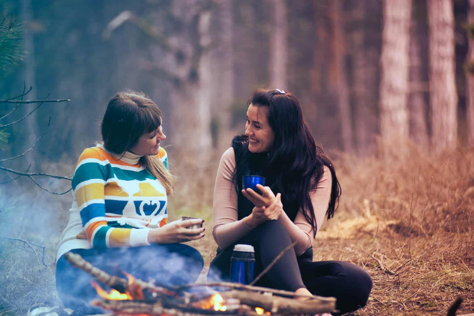 Deux femmes sourient assises près d'un feu de camp