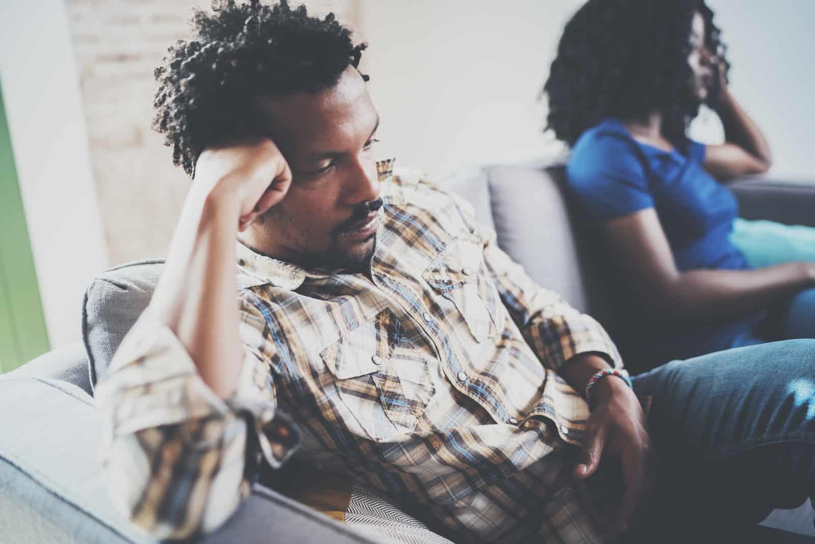 homme triste appuyé sur le canapé et assis près d'une femme