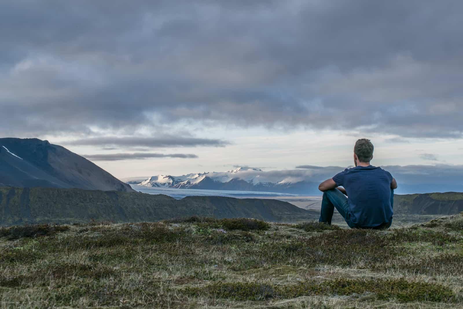 homme en chemise bleue assis au sommet d'une montagne