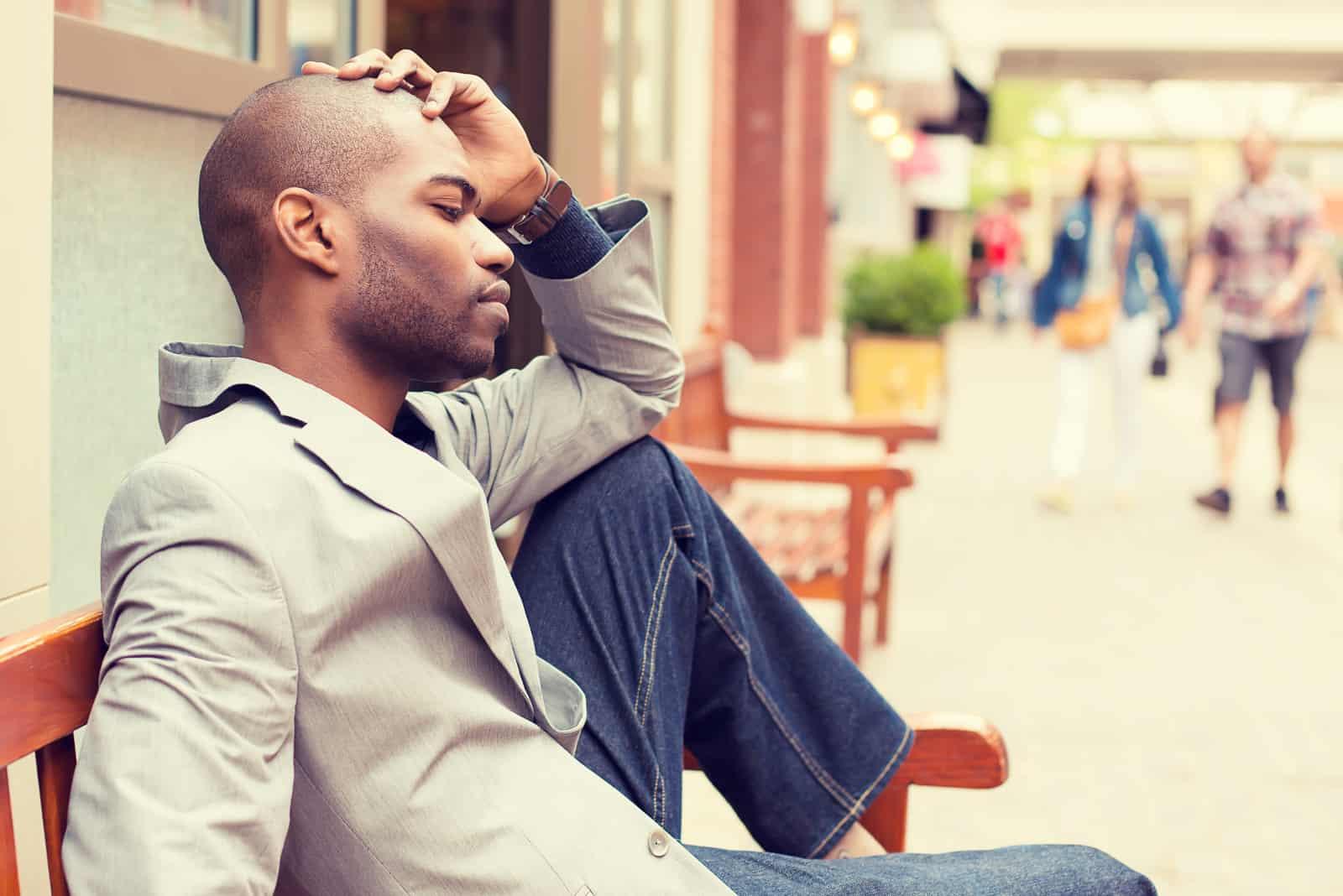 homme triste en blazer gris assis en plein air