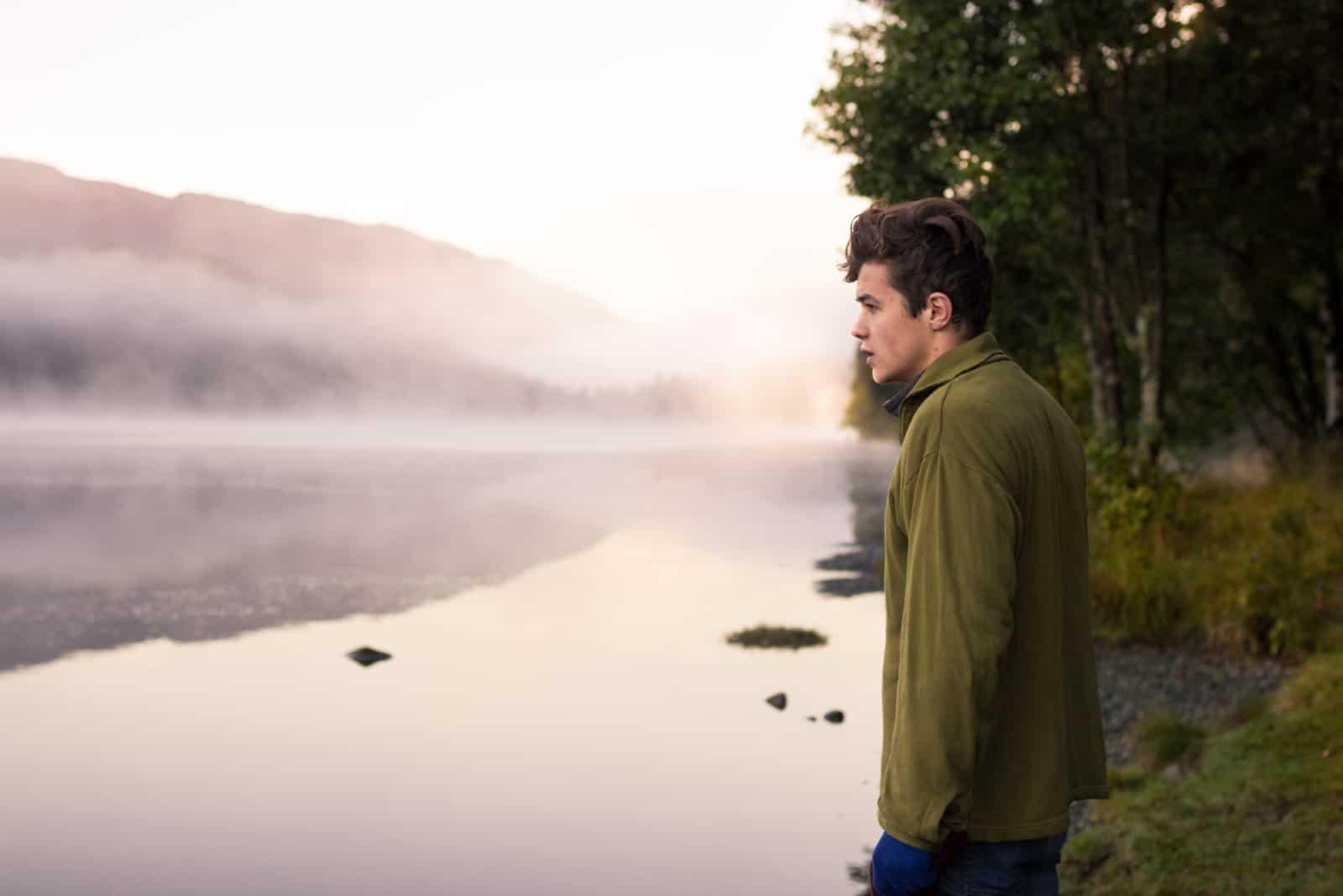 homme en veste verte debout près d'un lac