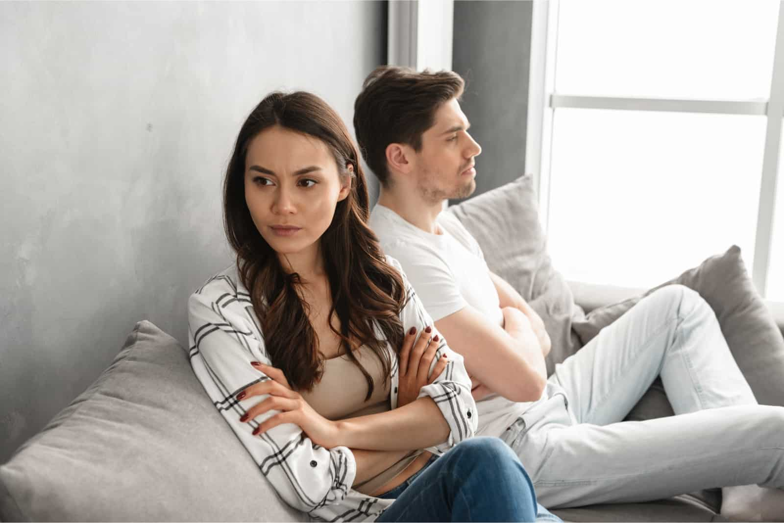 sad man in white t-shirt and woman sitting on couch
