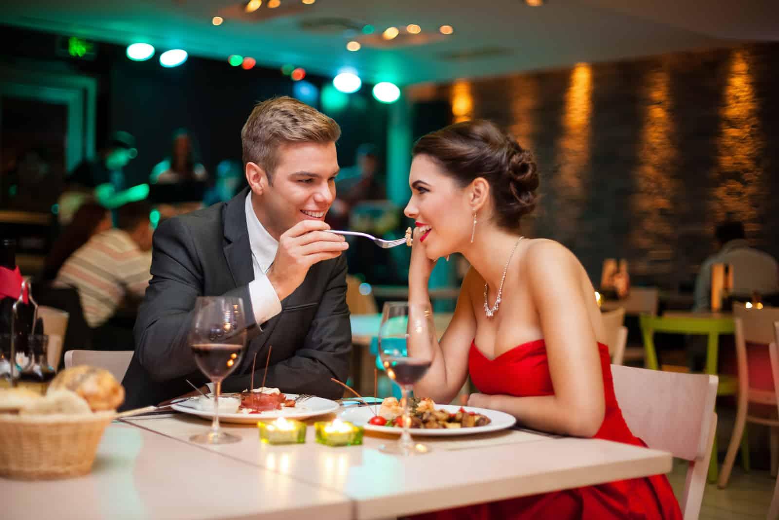 Homme élégant nourrissant une femme dans un restaurant