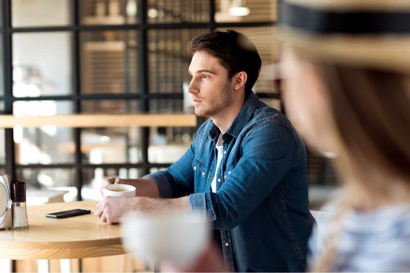 homme pensif avec une tasse de café à l'écart