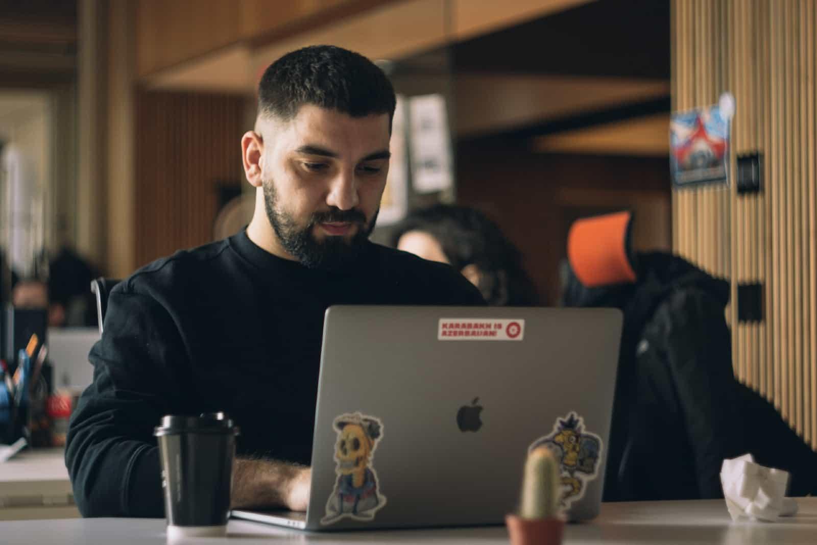 Homme utilisant un ordinateur portable assis à une table