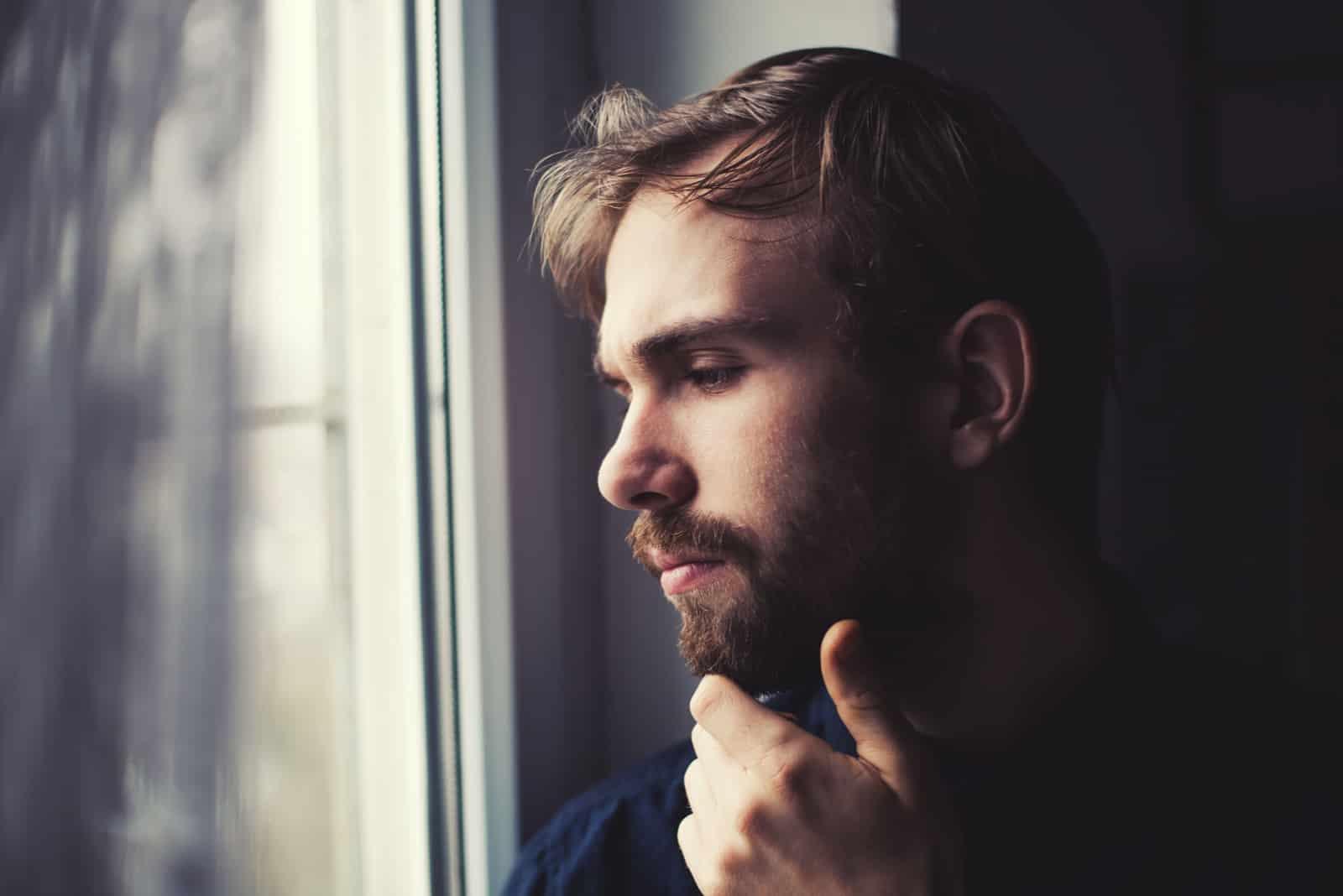 jeune homme regardant à travers une fenêtre