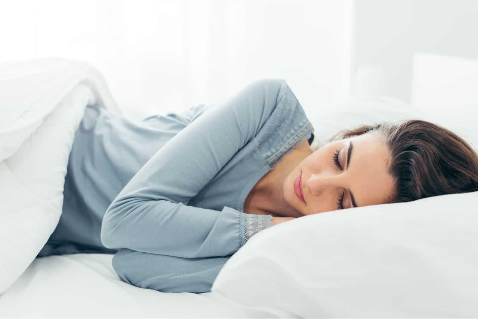 la femme est allongée dans son lit et dort