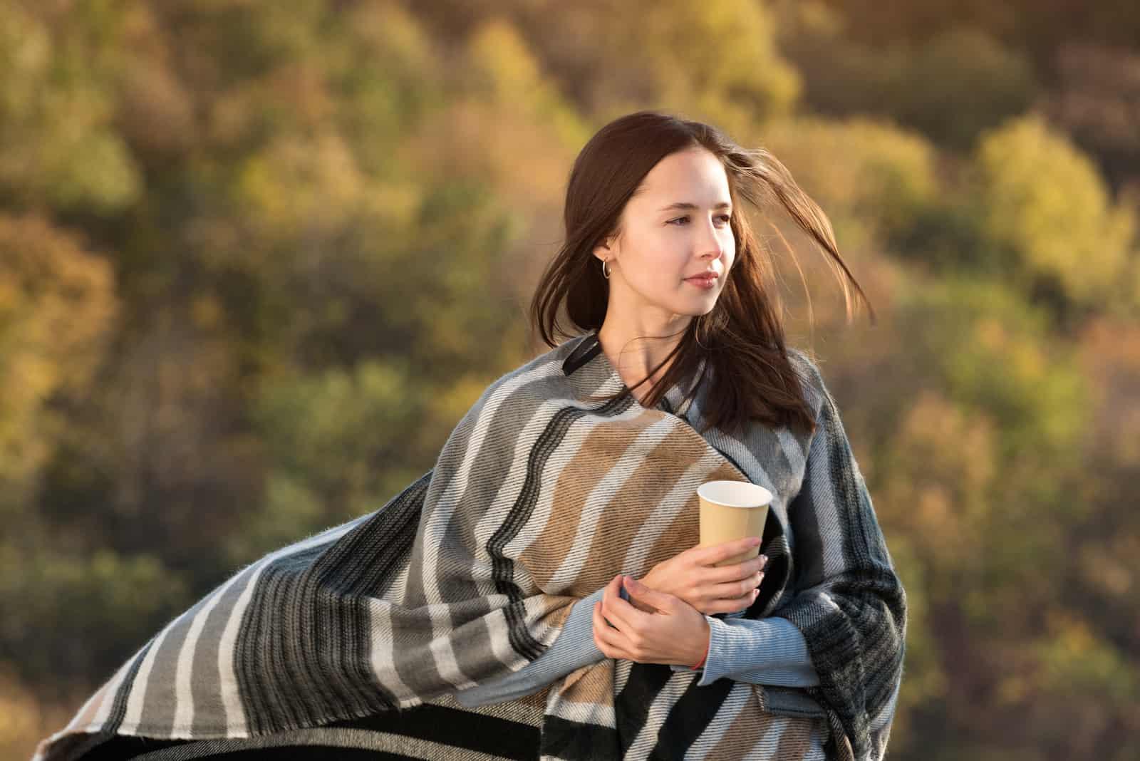 la femme est debout et tient un café à la main
