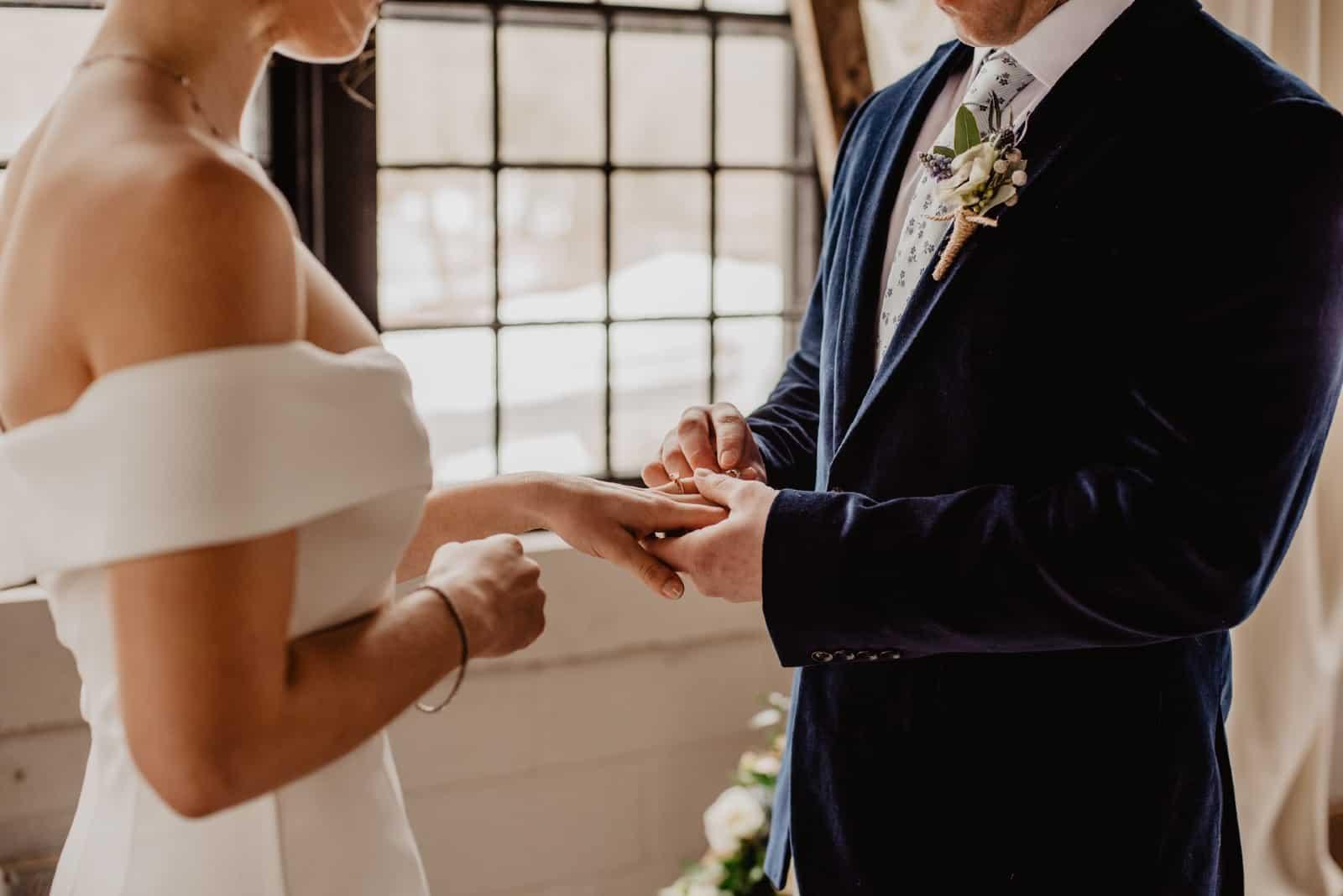 Le marié met l'alliance au doigt de la mariée