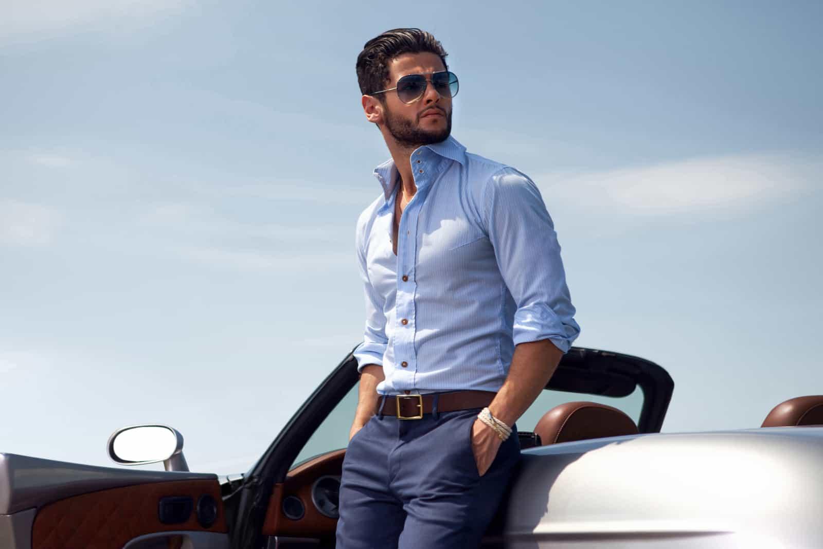 un bel homme en costume se tient appuyé contre une voiture