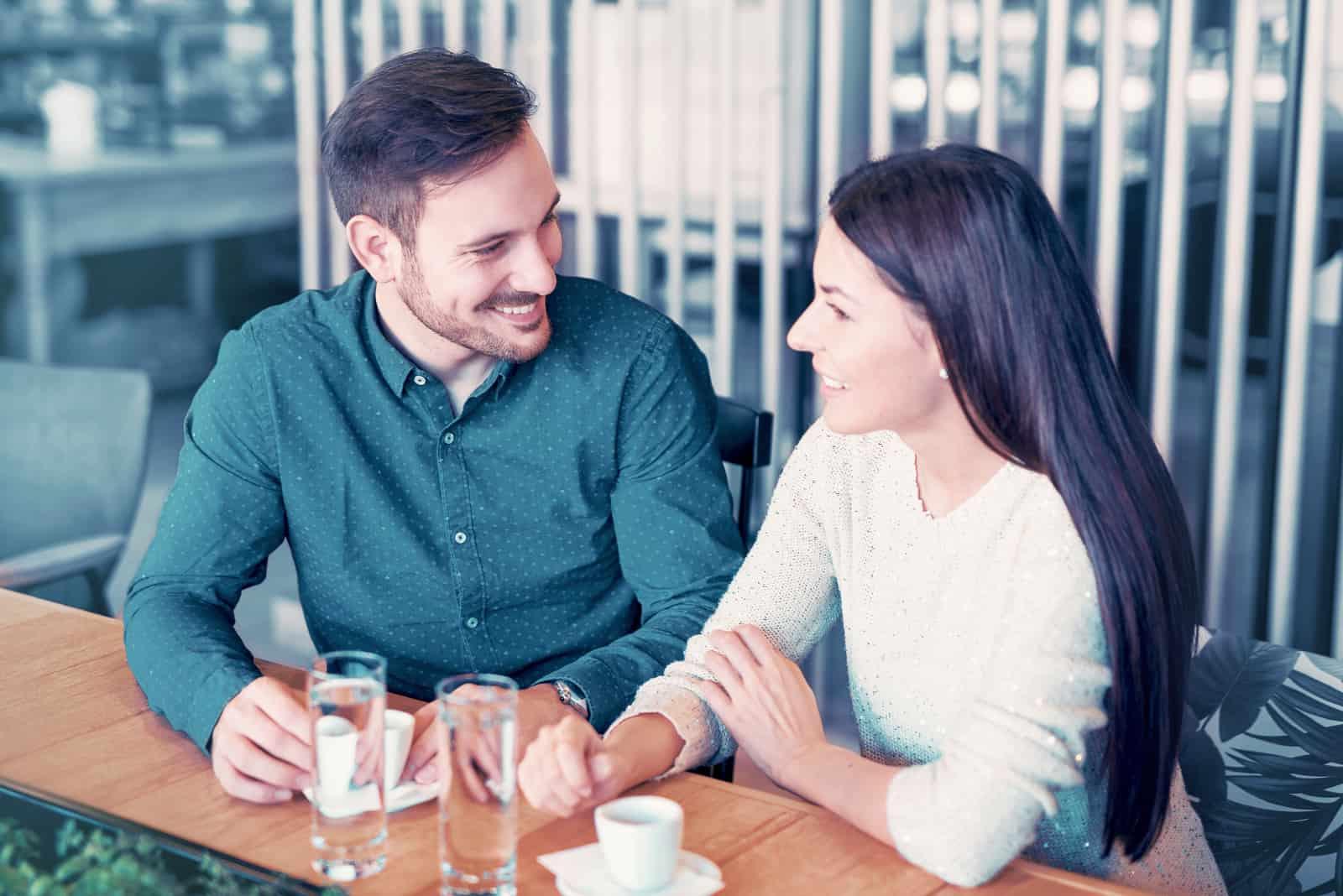 un couple amoureux assis à une table et parlant