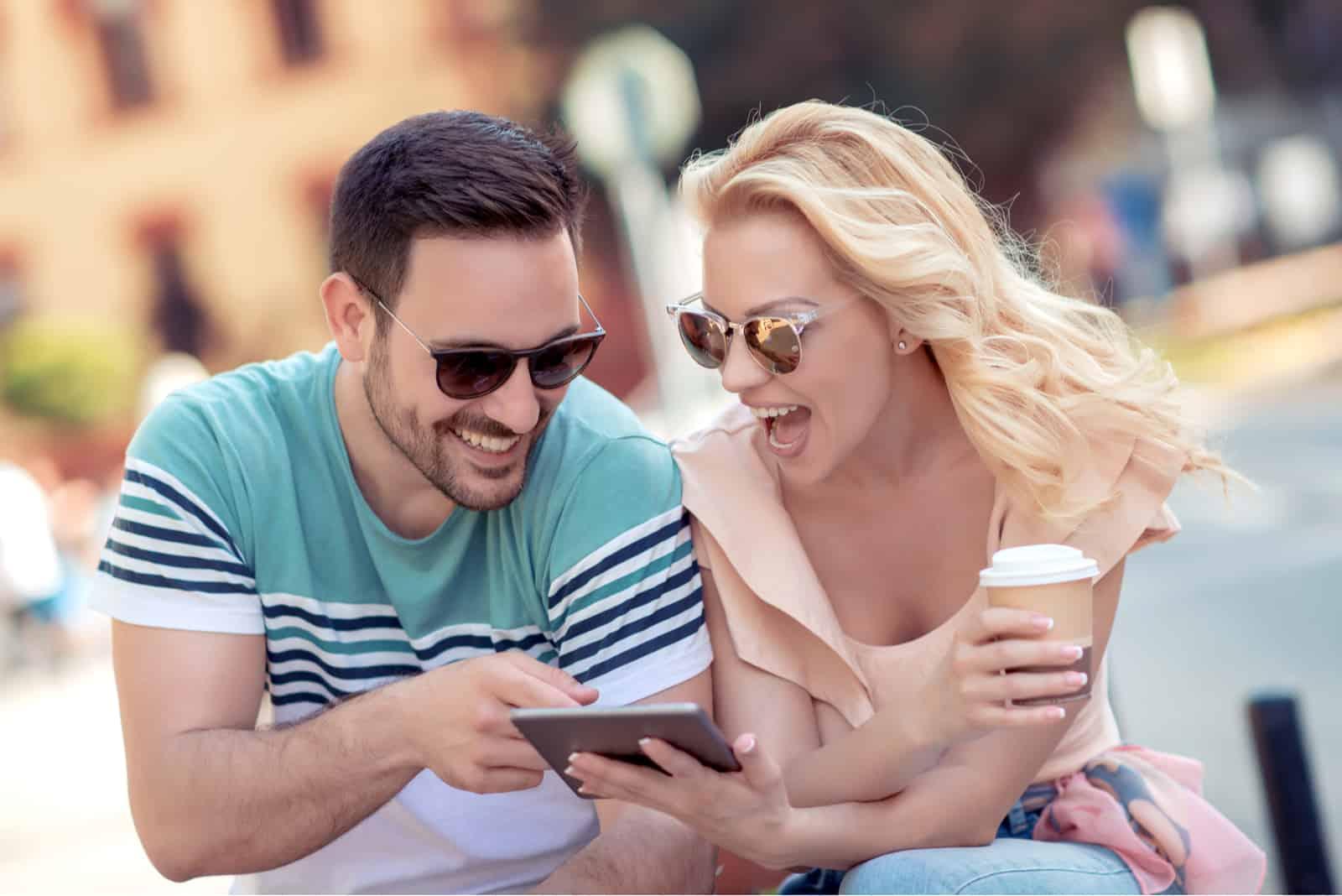 un couple amoureux assis dans les escaliers en regardant le téléphone et en riant