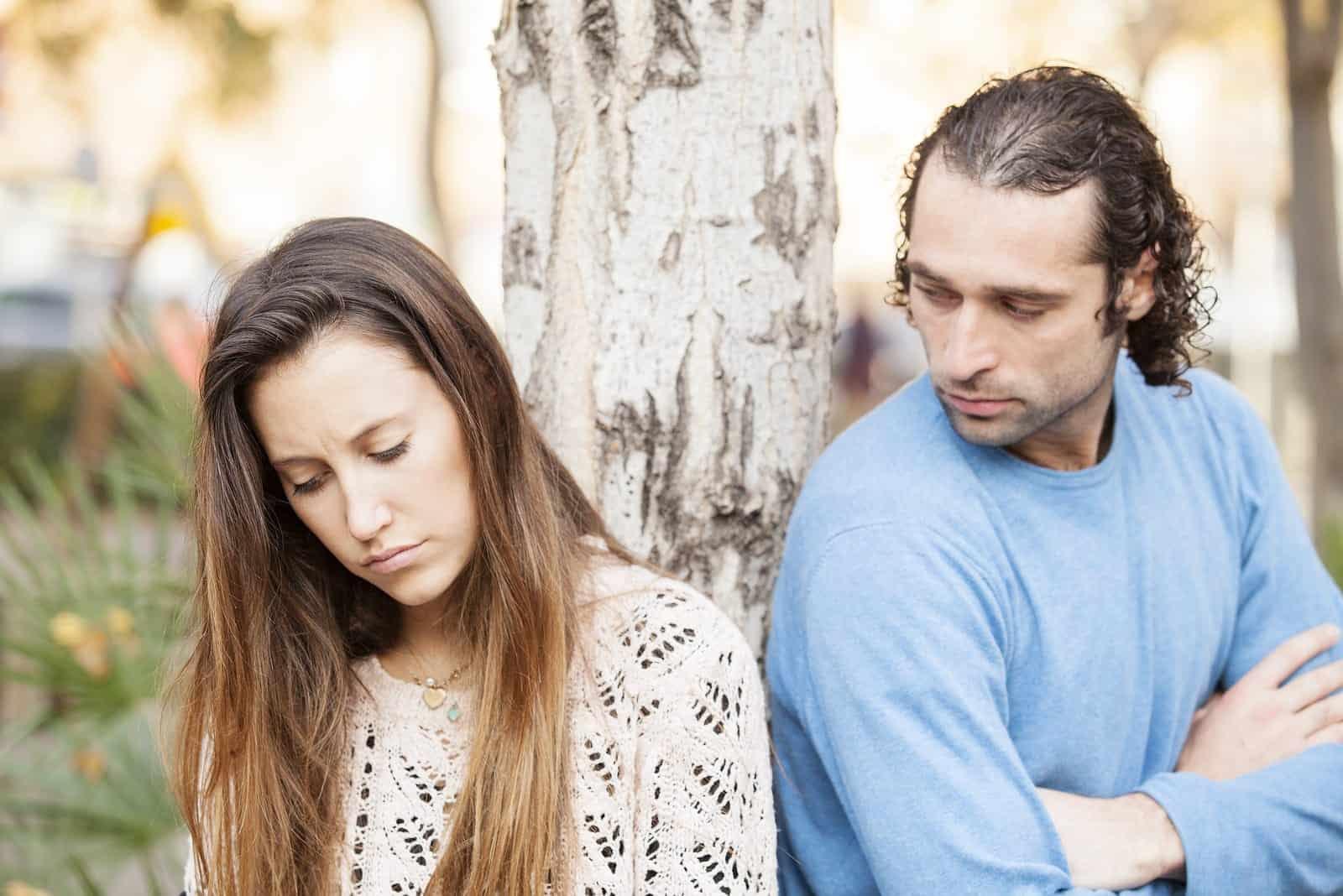 un couple d'amoureux tristes se tenant dehors près d'un arbre