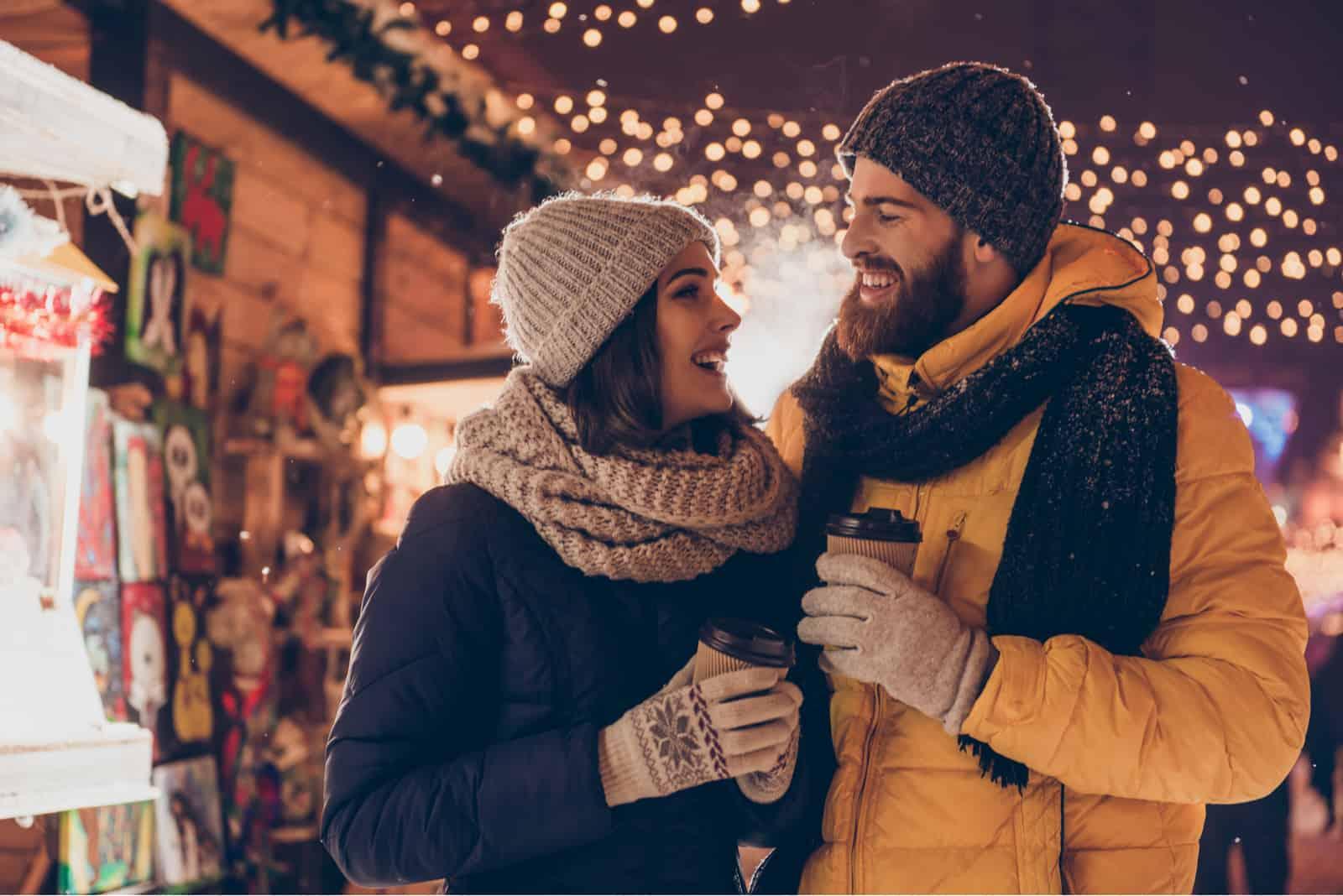 un couple souriant debout dans la rue tenant un café à la main
